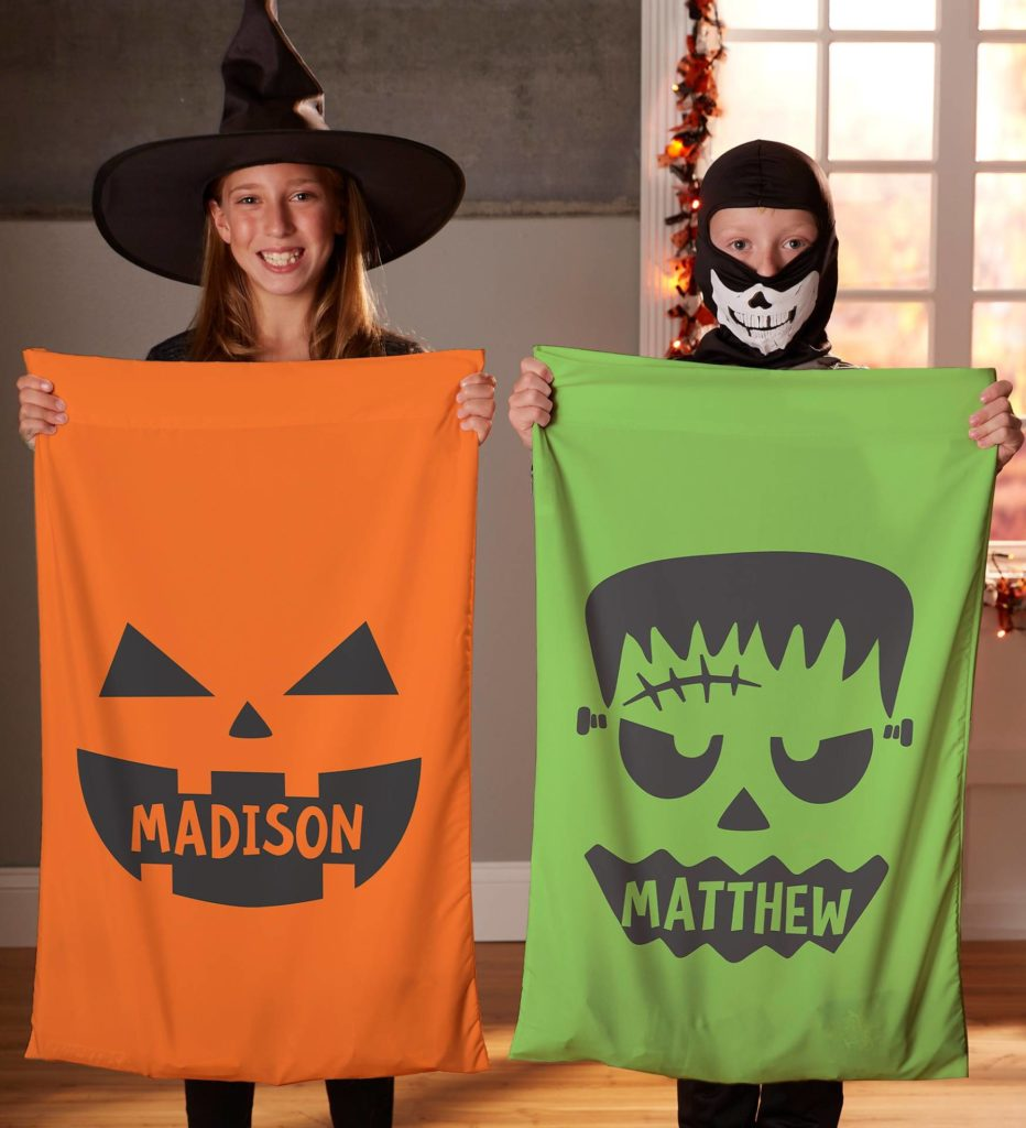 A photo of two children holding personalized spooky pillow cases, which are a great way to boost the Halloween decor of a bedroom.
